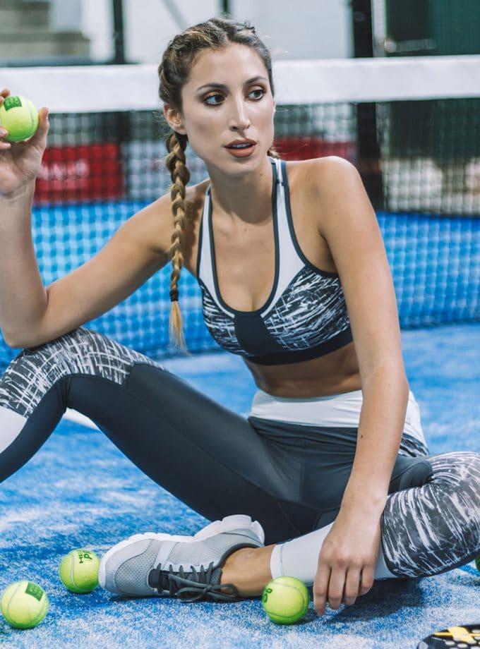Coordenado composto por leggings e sutiã desportivo de cor cinzenta com estampado e detalhes em branco.